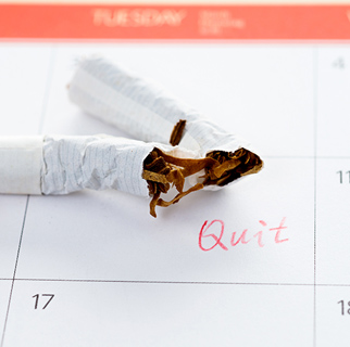 "close up image of a broken cigarette on top of a calendar date square with the word ""quit"" written in the square."